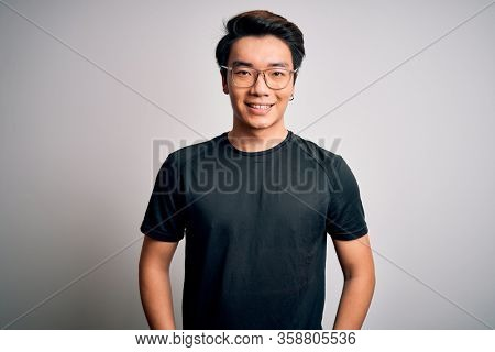 Young handsome chinese man wearing black t-shirt and glasses over white background with a happy and cool smile on face. Lucky person.