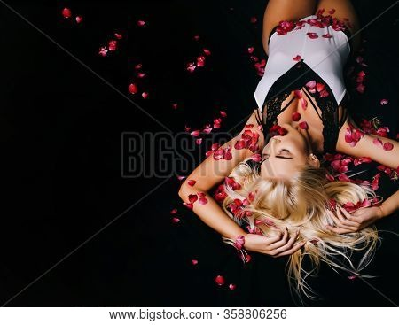 Attractive Girl In Bad With Rose Petals. Alluring Woman With Bright Makeup Bad. Pretty Sexy Blonde R