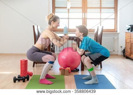 Family doing squats on floor at home during Covid-19 curfew staying fit