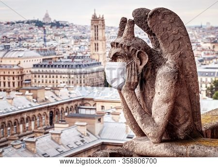 Covid-19 Coronavirus In France, Medical Mask On Gargoyle Of Notre Dame In Paris. Tourist Landmarks C