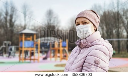 Woman At Playground With Surgical Mask On Face During Covid-19 Coronavirus Pandemic. People Wearing