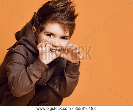 Little Brunet Model In Brown Dino Hoodie With Hood. He Is Growling And Scaring You, Posing Sitting S