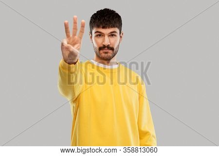 count and people concept - young man in yellow sweatshirt showing three fingers over grey background