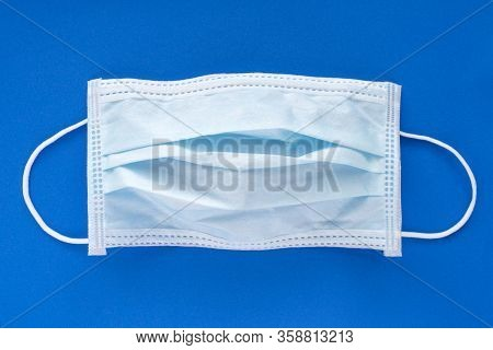 Typical 3 Ply Surgical Face Mask With Rubber Ear Straps To Cover The Mouth And Nose
