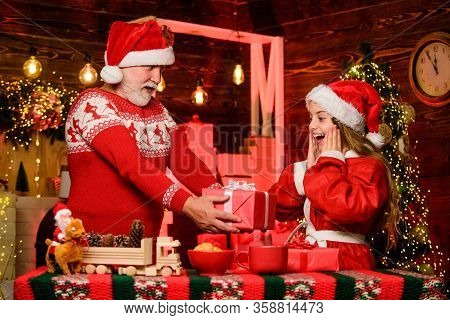 Santa Claus Generous. Child Enjoy Christmas With Bearded Grandfather Santa Claus. Happiness And Joy.