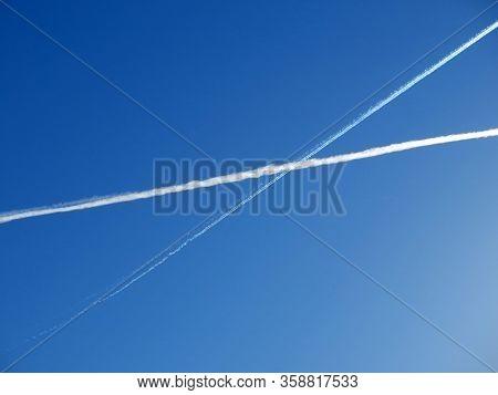 Two White Crossing Vapor Trails Against Blue Sky