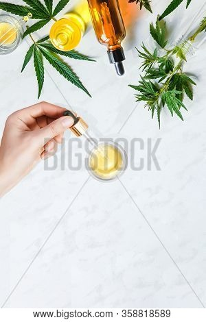 Glass Bottles Cbd Oil, Tincture And Hemp Leaves On A Marble Background. Female Hands Holding Pipette