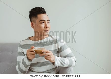 Asian Man Drinking Coffee When Sitting On Sofa At Home.