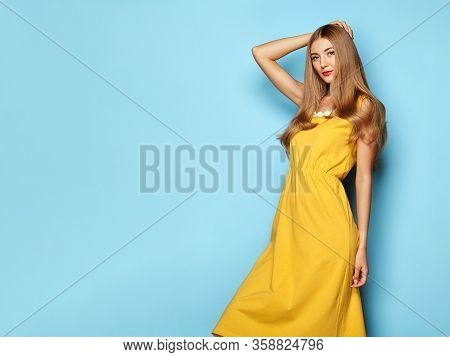 Blonde Young Woman In Yellow Spring Summer Dress. Lady In Stylish Summer Outfit. Girl Posing On A Bl