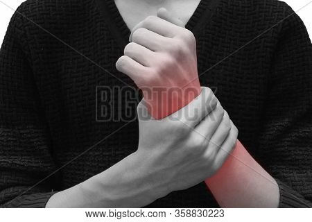 The Teenager Has A Sore Wrist. A Young Man Clings To His Wrist, Sharp Pain. Black And White Photo Wi