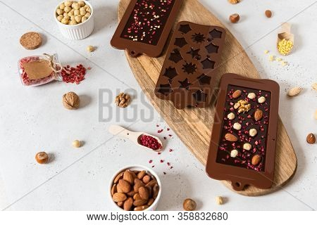 Raw Vegan Handmade Chocolate With Nuts And Dried Fruits In Molds. Chocolate Bars And Pralines On Whi