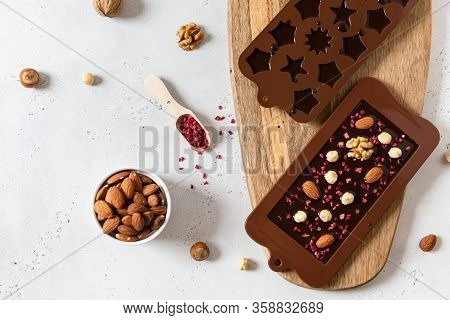 Handmade Dark Chocolate Bar And Candies In Molds With Nuts And Dried Fruits On White Background. Top