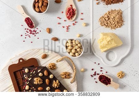Homemade Dark Chocolate Bars And Pralines In Molds With Dried Berries And Nuts On White Background.