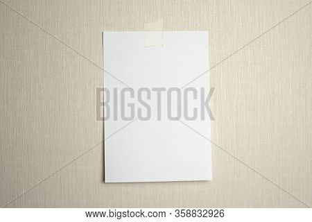 A4 White Sheet Of Paper Hanging On A Wall Glued With A Piece Of Paper Tape On A Light Background.