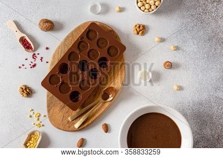 Raw Vegan Handmade Chocolate Candies In Mold With Nuts And Dried Fruits On White Concrete Background