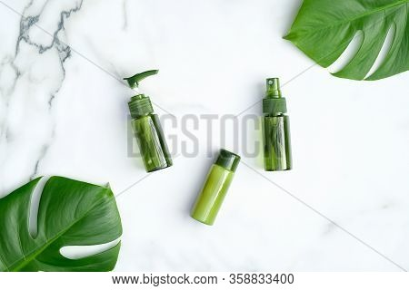 Green Cosmetic Bottles With Monstera Tropical Plant Leaves On Marble Background. Natural Organic Spa