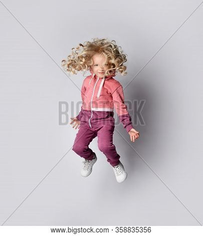 Playful Frolic Kid Girl In Stylish Modern Pink Gray Sportswear Hoodie And Pants Jumps High And Her C