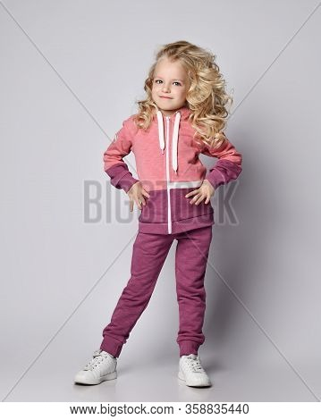 Beautiful Frolic Sly Smiling Curly Hair Blonde Kid Girl In Modern Fashion Pink Gray Sportswear Hoodi