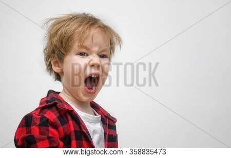 Child Boy Preschooler Yawns On A White Gray Background. Kid Woke Up And Did Not Sleep. His Hair Is D