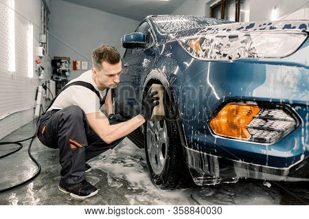 Car Washing And Detailing Photo. Caucasian Man Worker In Protective Overalls And Rubber Gloves, Wash
