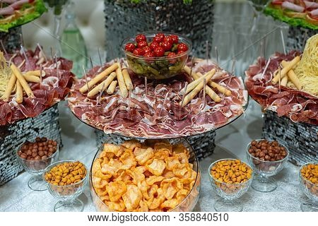 Banquet Table With Cheese, ?hips, Nuts, Cold Meats, Sliced Sausages, Cucumbers, Tomatoes. Variety Of
