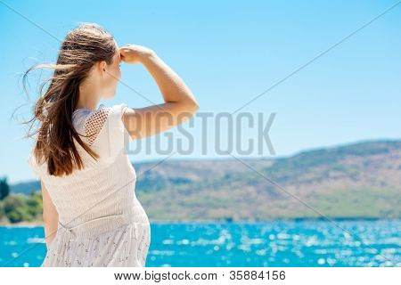 Young pregnant woman by the sea