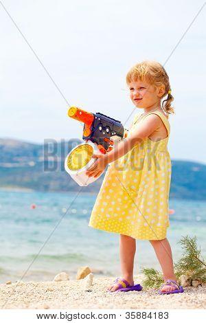 Small girl playing with water gun at the seashore