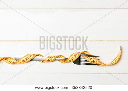 Diet And Healthy Eating Concept With Fork Wrapped In Measuring Tape On Wooden Background. Top View O