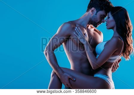 Sexy Young Couple Embracing While Standing Face To Face Isolated On Blue