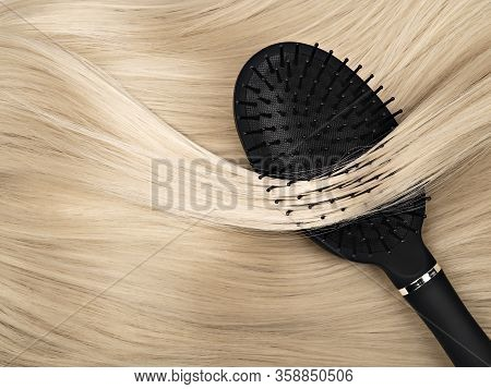 Closeup Of Black Hair Brush Lying On Straight Shiny Blond Hair. Hair Care Concept. Abstract Backgrou