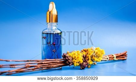 Anti Aging Serum In Glass Bottle With Dropper On Blue Background And Dry Flowers . Facial Liquid Ser