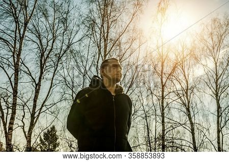 Portrait Of Man In Front Of Birches In The Rays Of The Bright Spring Sun. Low Angle View Of Male In