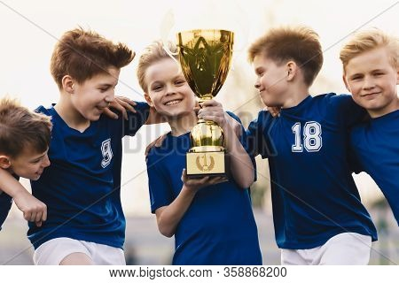 Children Winning Soccer Tournament. Group Of Happy Boys Holding Golden Trophy. School Sports Team Ce