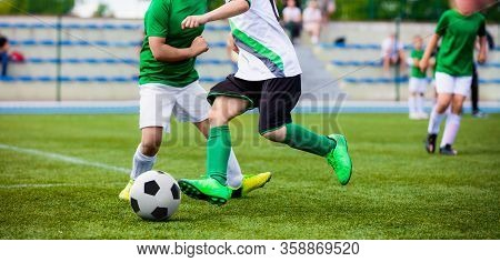 Running Football Soccer Players. Sports Competition Between Youth Soccer Teams. Young Boys In Hard D
