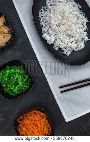 Rice With Korean Carrots, Soy Asparagus And Chuka On White Napkin On Black Background Top View.