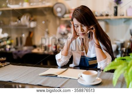 An Asian Barista Woman Is Stressed Because Of Economic Conditions And Covid-19 Or Coronavirus Has Ca