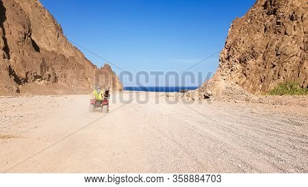 Desert In Egypt. Rocky Sand Hills. A Lone Tourist On An Atv In The Desert Against The Background Of