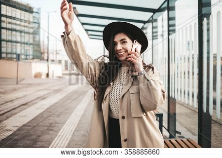 Girl Talking On The Phone And Waving While Standing At The Bus Stop