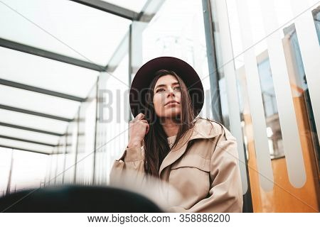 Pensive Woman In Hat And Coat Sitting At The Bus Stop