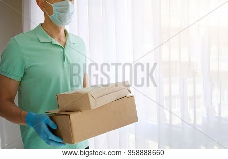 A Man A Medical Mask And Blue Rubber Gloves With A Box, A Parcel In His Hands. Food Delivery During