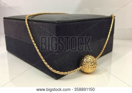 Thick Gold Chain With A Ball Pendant On A Brown Jewelry Box. Template For The Design Of The Jewelry