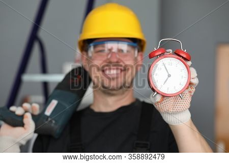 Male Builder Helmet Laughing Showing Alarm Clock. Performance Repair Work Within Specified Period. N