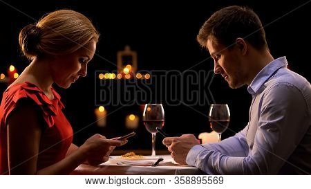 Addicted Couple Using Smartphones, Ignoring Each Other On Romantic Dinner