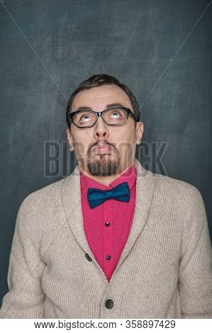 Doubting Funny Teacher Or Businessman Looking Up On Blackboard