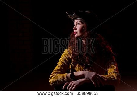 Portrait Of Elegant Woman With Long Hair Hat And In Yellow Sweater And Dark Background. Model Posing