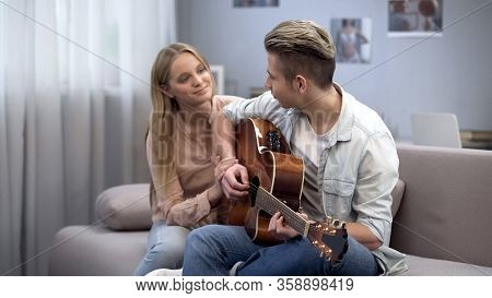Teen Student Playing Guitar And Girlfriend Hugging Him, Romantic Love Confession