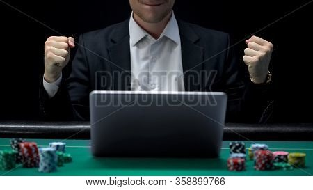 Gambler Playing On Laptop And Showing Success Gesture, Winning Bet, Fortune