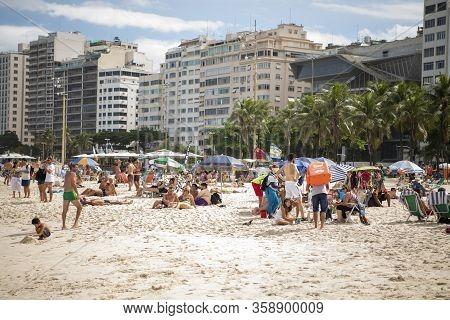 Rio De Janeiro, Brasil-  February 28, 2020: Citizens Sunbathe On The Beach Of Copacabana