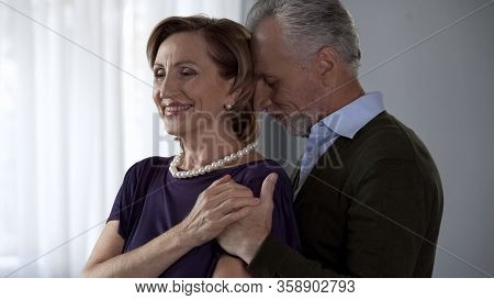 Retiree Man Holding Wife By Shoulders From Behind, Happy Moments Together