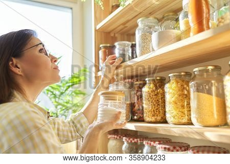 Food Storage In Pantry, Woman Holding Jar Of Sugar In Hand. Pantry Interior, Wooden Shelf With Food
